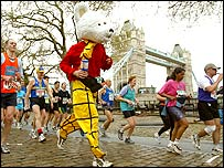 A runner dressed as Rupert Bear passes Tower Bridge during the London Marathon