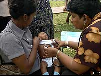 Doctor (R) tends to 15-day-old baby in Kahawa, Sri Lanka