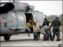 US Navy personnel escort refugees from the hard-hit Meulaboh district who have been evacuated to Banda Aceh