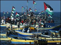 Palestinian flags fly on fishing boats on the shore of Gaza city