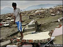 A teenager stands among the ruins of his home in Banda Aceh, Indonesia