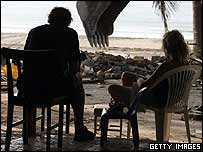 Swedish tsunami survivors watch a digger on Patong Beach, Thailand