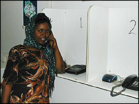 A woman using a phone in a Simu ya watu kiosk