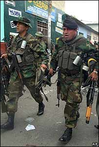 Polic�as peruanos cargan las armas de los insurgentes rendidos.