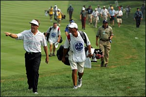 Stuart Appleby (L) leaves the course with his caddie