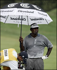 Vijay Singh shelters under an umbrella