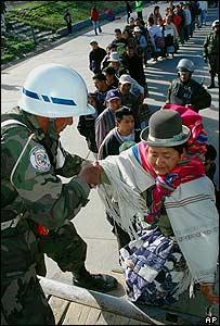 Soldado boliviano ayuda a una se�ora a subir a un transporte de emergencia.