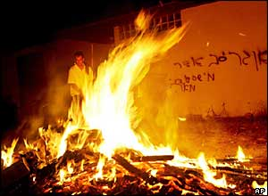 A Jewish settler burns possessions in front of a house in Elei Sinai, northern Gaza