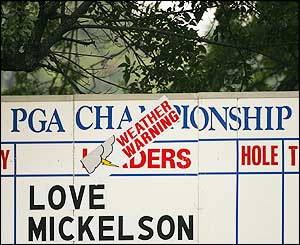 A weather warning sign on a fourth-round scoreboard at Baltusrol