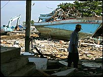 A man walks through a destroyed house in the devastated fishing village Ban Nam Khem of Phuket, Thailand, as people start clean up.