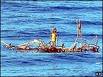 Rizal Shahputra stands on the tree branches and waves to a cargo ship after being spotted by the crew of a container vessel,  Monday, Jan. 3, 2005.