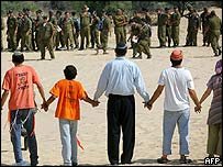 Israeli settlers link arms to prevent Israeli soldiers from entering the Gaza Strip settlement of Neve Dekalim