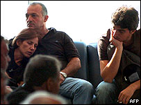 Bereaved relatives wait at Larnaca Airport, Cyprus, to fly to Greece