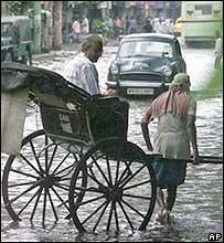 A rickshaw puller takes his customer through a flooded street after rains in Calcutta
