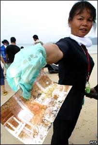 A Thai volunteer displays a photo of a foreign tourist found on Patong beach