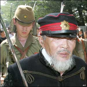 A Japanese army veteran, right, dressed in military uniform, leaves the Yasukuni shrine  - 15/8/05
