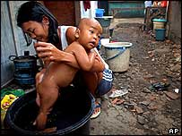 Mother in slum washes baby   AP