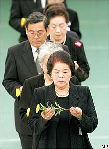 Japanese war bereaved, holding a chrysanthemum, wait in a queue at ceremony in Tokyo - 15/8/05
