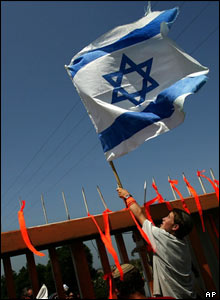 A settler places an Israeli flag on top f the main gate of Netzer Hazani
