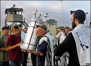 Israeli settlers carry a Torah scroll