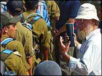 A Jewish settler remonstrates with Israeli soldiers