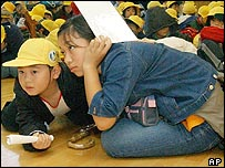 Children crouch in the corridor of their Kawaguchi elementary school at Kawaguchi, northern Japan, on Monday November 8, 2004.