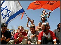 Israeli settlers seat at the gate of the Gaza Strip settlement of Ganei Tal