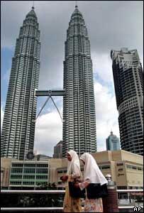 Two women walk past Petronas Towers in Kuala Lumpur, Malaysia