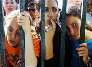 Israeli girls watch Israeli police making a line in front gate of the Southern Gaza settlement of Neve Dekalim
