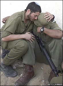 Two soldiers comfort each other as the Israeli army evacuates a synagogue in the Nisanit settlement