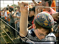 A young settler holds on to the fence surrounding Neve Dekalim settlement in Gaza