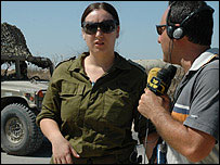 A radio reporter speaks to an Israeli soldier