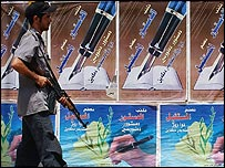 An Iraqi policeman stands guard near pro-constitution posters in Baghdad