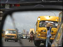 People carrying loads walk past transport buses in Lagos, Nigeria