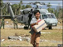 A boy carries relief aid in Aceh, Indonesia