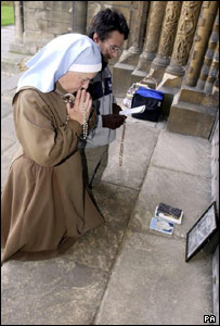 A nun and her friend kneel outside Lincoln Cathedral