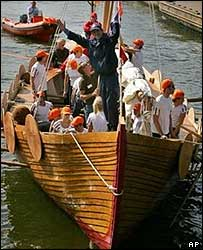American Rob McDonald waves from stern of Viking longboat