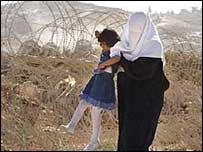 Israeli security barrier in the West Bank, woman and child watching