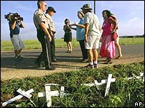 Texas officers and peace activists beside the damaged crosses