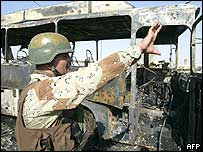 An Iraqi soldier by the wreckage of a bus in Baghdad