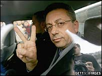 Mustafa Barghouti makes a victory sign as he is driven away in an Israeli police car
