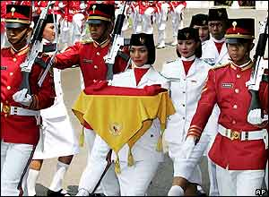 Escorted by honour guards, flag bearer Dona Olianda Vitri, centre, of Aceh province carries an Indonesian National Red-White flag to be hoisted during celebrations, Aug. 17, 2005.