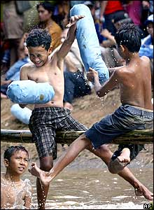 Indonesian youths attempt to knock each other down into the water during a pillow fight game at a city canal in Jakarta, Indonesia, Wednesday, Aug. 17, 2005.