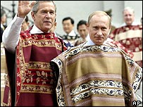 George W Bush and Vladimir Putin, wearing traditional Chilean ponchos