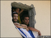Jewish settlers fly an Israeli flag from a house they have blockaded themselves in to in Morag settlement, Gaza
