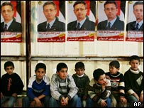 Palestinian boys in Hebron sit beneath posters of Mustafa Barghouti