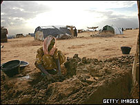 Displaced Sudanese woman prepares mud bricks. File photo