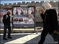 Palestinos frente a carteles electorales.