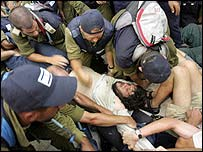 Man being carried away from Neve Dekalim synagogue