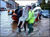 Elderly woman being carried by rescue workers in Carlisle